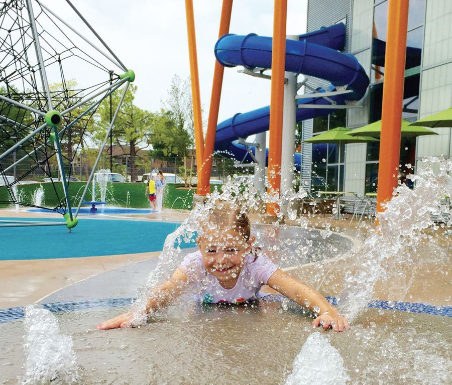 Little girl making a big splash on the splash garden at the Tandy Family YMCA, in Tuls, OK, and the decorative concrete built with Bomanite Exposed Aggregate Systems using Bomanite Revealed and Bomanite Sandscape Texture.